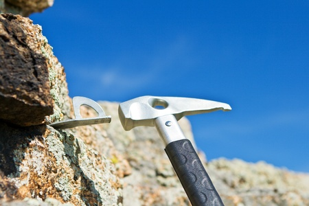 alpinism: The hand and hammer of the rock-climber hammers in hook Stock Photo