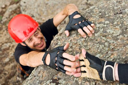The rock climber gives hand for help to the partner photo