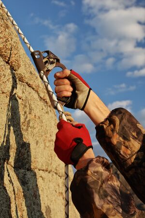 Hands the rock-climber with rope and equipment climbs on top photo