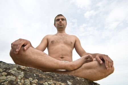 A young man doing yoga in the outdoor photo