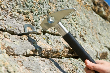 rockclimber: The hand and hammer of the rock-climber hammers in hook Stock Photo