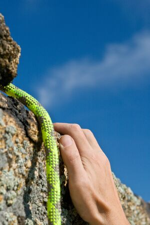 brink: Hand of climber on brink in rock reaching top Stock Photo