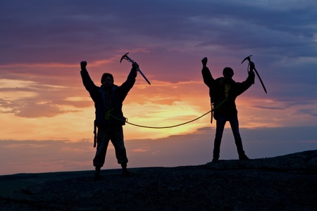 ice climbing: Sportsmen at top of mountain against sunset with hands up