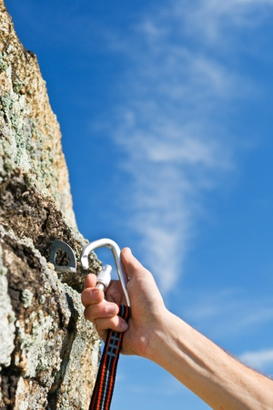 carabiner: The hand of climber hangs up carbine in hook on rock Stock Photo