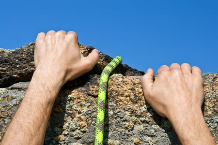 Hands of climber on brink in rock reaching top