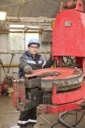 drill floor: The young driller a wearing spectacles and protective suit drills well Stock Photo