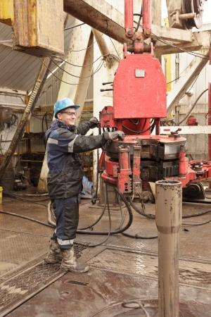 trabajador petrolero: El perforador funciona la herramienta en el lugar de trabajo Foto de archivo