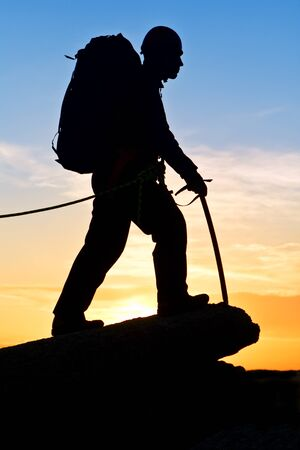 ice axe: The rock-climber walking on mountain top on decline