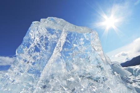 Beautiful transparent ice of Lake Baikal against the clear dark blue sky and a bright sun with rays of light