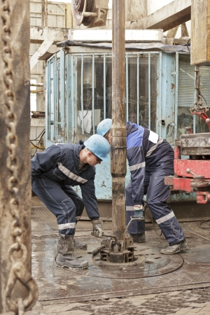 Two roughnecks do the equipment for fixing of rig pipe photo
