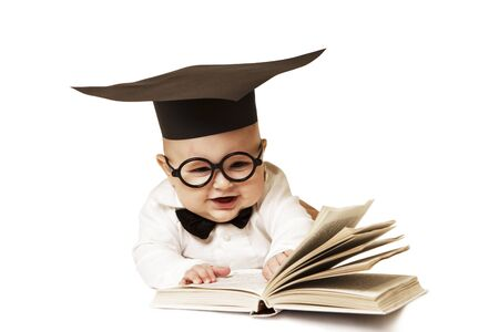 The laughing small child in the academic cap and with the book Stock Photo