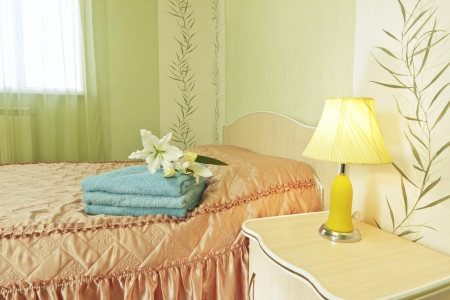 Beautiful bed with poloyenets and flowers  It is ready to welcome new guests Stock Photo - 15623177