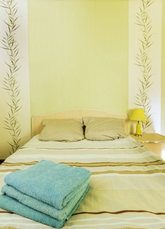 Empty pure bed with linen pile in light room
