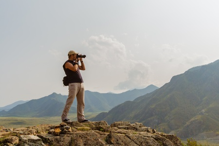 photographing: Professional photographer in the mountain makes shooting in sunlight day