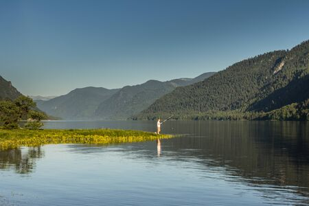 ashore: Early morning in mountains. The lake and the fisherman ashore with fishing tackle