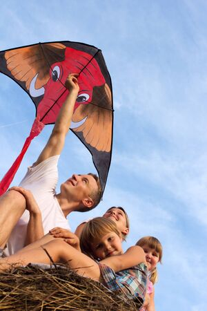 The family outdoors flying kite in the sky photo