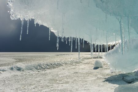 hummock: Big beautiful ice floe with icicles in the foreground on Baikal. Russia.
