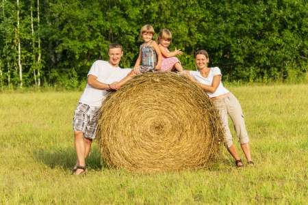 Happy family with children on haystack in sunny day