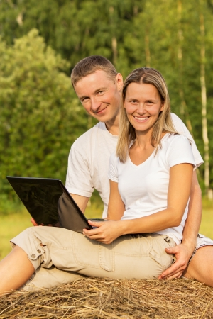 Young people with the laptop on haystack Stock Photo - 17535054
