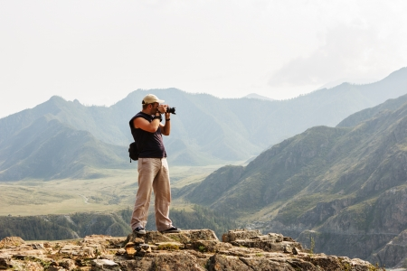 Beautiful landscape with the silhouette of photographer on background of mountains Standard-Bild