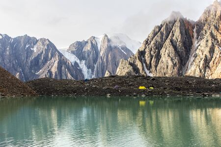 Camp of rock-climbers on the bank of reservoir highly in mountains Stock Photo - 17595880