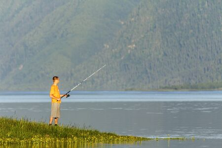 Beautiful landscape of the mountain lake with the fisherman in the foreground Stock Photo - 17535055