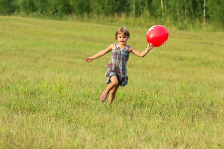 The girl plays with ball outdoors in sunlight photo