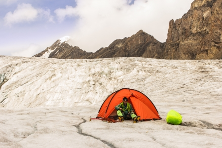 The climber in tent in mountain camp in tent on glacier Stock Photo - 17644576