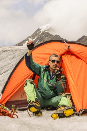 The climber sits in tent and causes the help highly in mountains Stock Photo - 17644572