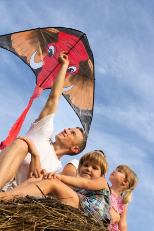 The happy family astride hay flies kite. photo