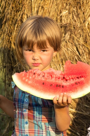 mimicry: Portrait with mimicry of the child at foods of sweet water-melon