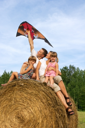 haystack: Family from four people against the blue sky flying kite