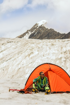 recreational climbing: The climber in tent on glacier against beautiful Mountains Altai Stock Photo