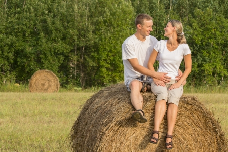 Young couple outdoors sit in embrace on haystack photo