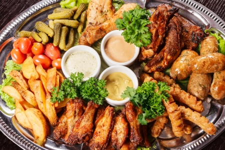 Huge choice of different meat dishes on one plate with spices and vegetables photo