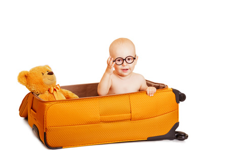 The child with toys with round points sits in suitcase