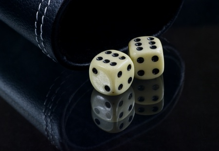 Two standard six-sided pipped dice with rounded corners on black background. Stock Photo - 8479653