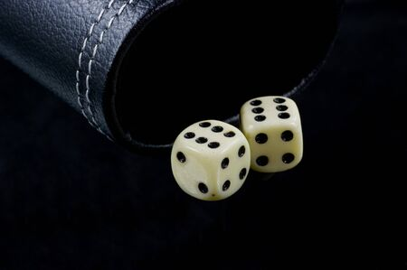 Two standard six-sided pipped dice with rounded corners on black background. Stock Photo - 8479650