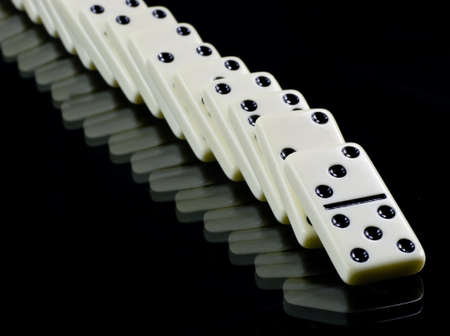 toppled: Toppled dominoes,  white tiles on black background.