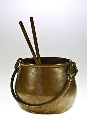 Old copper pot with two chopsticks on white