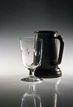 pewter mug: Pewter mug and wine glass on reflective background