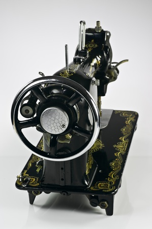 Old black sewing machine on white background photo