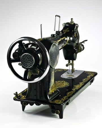 Old black sewing machine on white background