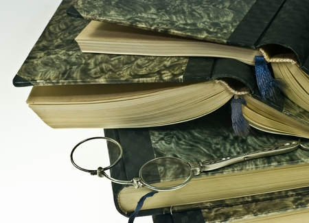 Stack of old books and lorgnette Stock Photo