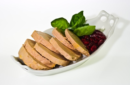 Sliced foie gras with cumberland sauce and basil leaves photo