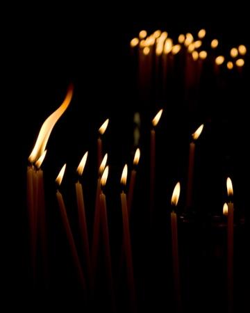 Burning votive candles in a Greek church over dark background.