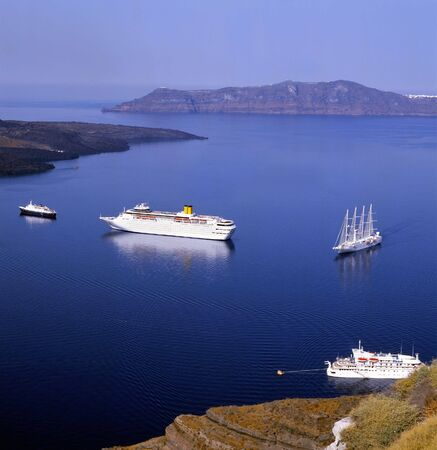 aegean: Sailboats at the entrance to Santorini harbour in blue calm sea, greece, europe