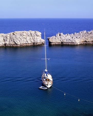 rhodes: Sailboat moored off the coast of the village of Lindos on the greek island of Rhodes Stock Photo