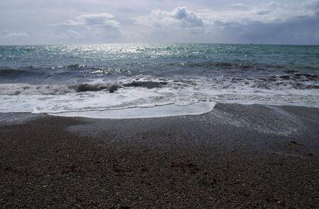 beach shingle: La costa luce con chiaro di luna con il mare a venire in pi� di una spiaggia ghiaiosa