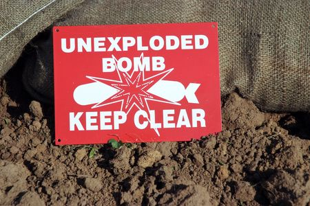 bomb sign: Unexploded Bomb sign next to sand bags and soil Stock Photo